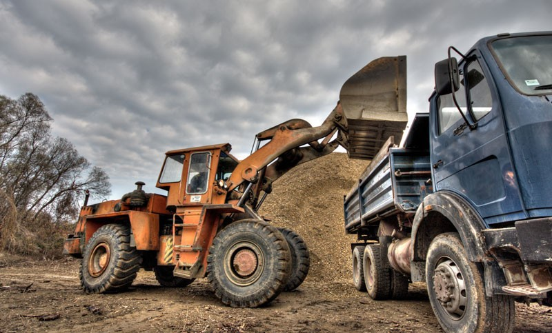 Excavator loading excess soil into a truck.