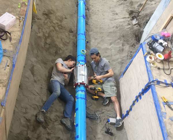 Researchers from the Cambridge Centre for Smart Infrastructure and Construction attach sensors to a test pipe in Cornell's Geotechnical Lifelines Large-Scale Testing Facility.
